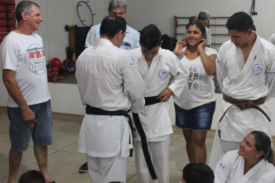 Sansei. vilson colocando faixa preta no karateca marcos jr.